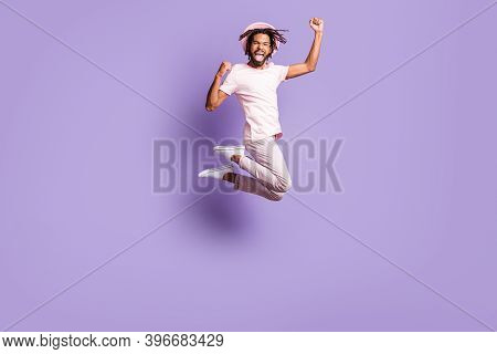 Full Size Photo Of Young Afro Excited Happy Man Guy Wear Pink T-shirt Violet Trousers Pants Jump Fly