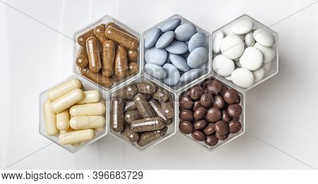 Various Medical Capsules And Tablets In Hexagonal Jars