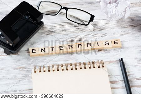 Enterprise Concept With Letters On Cubes. Still Life Of Businessman Workspace. Flat Lay Vintage Wood
