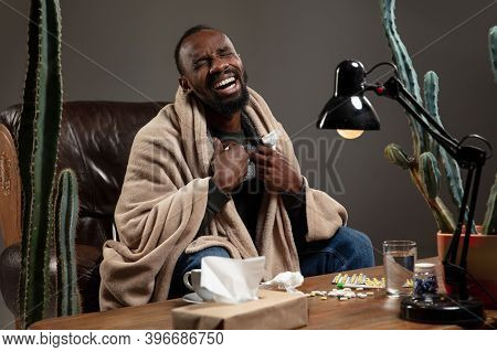 Fever. Young African-american Man Wrapped In A Plaid Looks Sick, Ill Sitting On Armchair At Home Ind