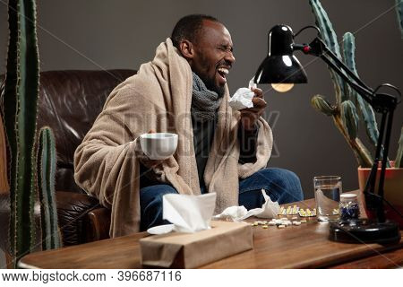 Runny Nose. Young Man Wrapped In A Plaid Looks Sick, Ill, Sneezing And Coughing Sitting On Armchair