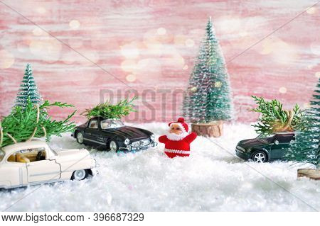 Toy Santa In The Forest Among The Snowdrifts, Waves To Cars That Are Delivers Christmas Trees. Magic