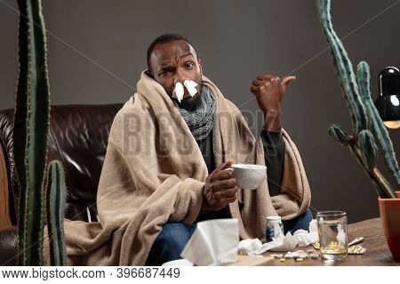 Runnynose. African-american Man Wrapped In A Plaid Looks Sick, Ill Sitting In Armchair At Home Indoo