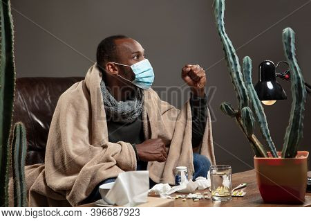 Protective Face Mask. Young Man Wrapped In A Plaid Looks Sick, Ill Sitting In Armchair At Home. Heal