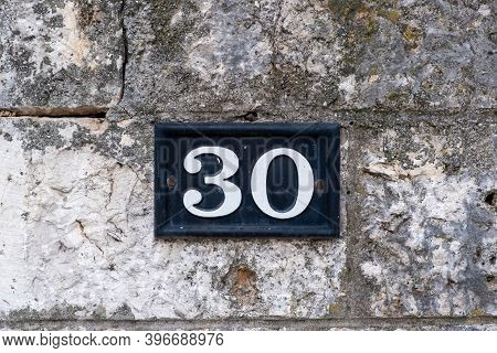 Street Number Thirty. Digit 30 White Color On Metal Vintage Plate Mounted On Stone Wall. Traditional