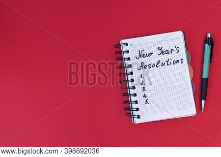 Writing In A Notebook New Years Resolutions On Red Background. New Years Resolutions Concept. Flat L