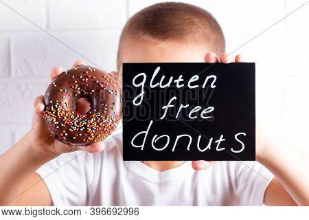 Child Boy With Gluten Free Healthy Chocolate Donut. Kid With Donut. Gluten-free, Soy Free, Lactose-f