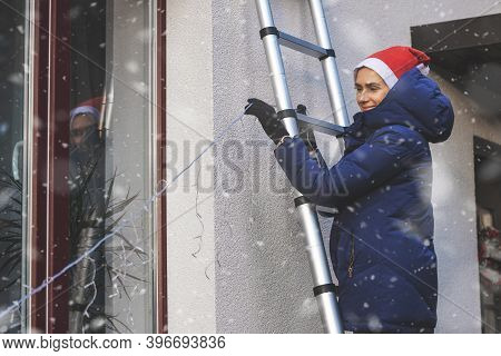 Woman With Santa Hat Standing On Ladder And Decorating House Exterior With Outdoor Christmas String