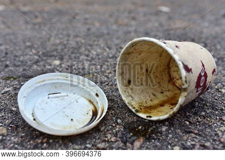 Crumpled A Paper Coffee Cup On Asphalt. Discarded Disposable Coffee Cup With A Plastic Lid On Road.