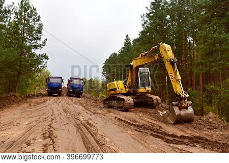 Dump Trucks And Excavator Work On Road Construction In A Forest Zone. Tipper Truck Transport Sand Fo