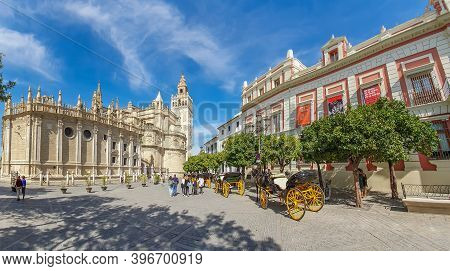 Seville, Spain - October 18. 2020: Horse Drawn Carriages At Plaza Triunfo With Tourists At The Back