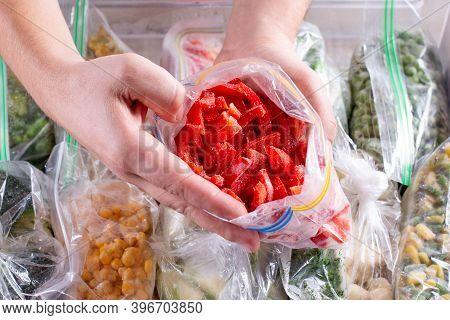 Frozen Red Peppers In Hand, Closeup. Frozen Vegetables In A Plastic Bag In Freezer