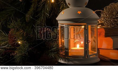 White Lantern With A Burning Candle. Nooks, Christmas Tree Branch And Lights On Background. Night Da