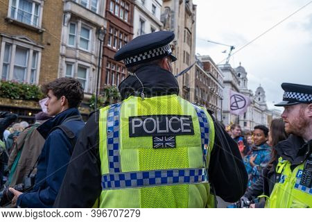 London, Uk - October 18, 2019: The Back Of A Police Officer Stood Patrolling At An Extinction Rebell