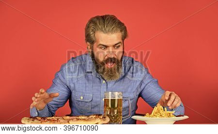 Bearded Man With Beer And Pizza. Italian Food. French Fries. Guy In Bar Drinking Beer Glass And Eati