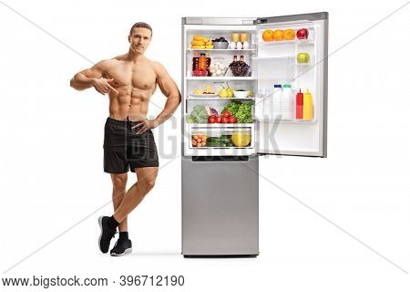 Full length portrait of a topless man pointing at his muscles and leaning on a fridge with healthy food isolated on white background