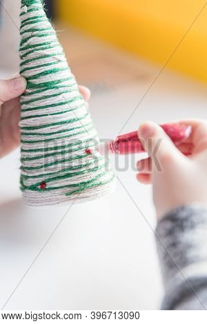 Hands Of A Little Girl Creating Thread Christmas Tree.handmade Christmas Knitted Gift.christmas Tree