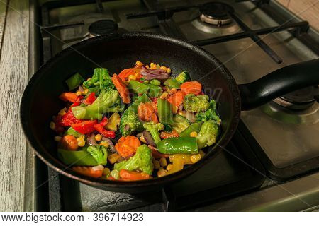 Lots Of Colorful Vegetables Are Fried In A Frying Pan On The Kitchen Stove. Carrots, Capsicum, Peppe
