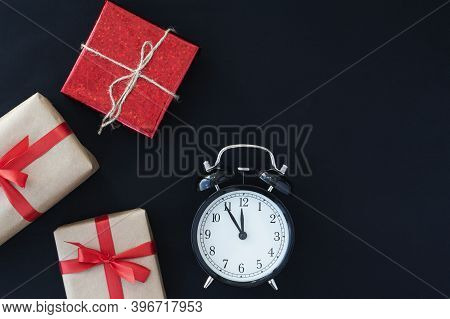 Black Friday Concept. Top View Of Alarm Clock, Three Giftboxes With Ribbon On Black Background, Copy