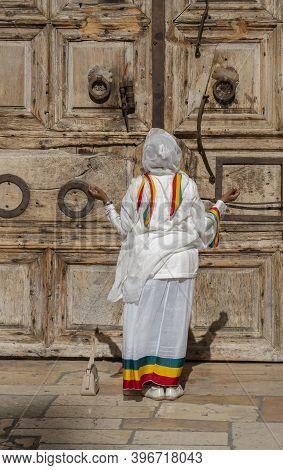 Jerusalem, Israel - November 21st, 2020: A Woman Praying At The Closed Doors Of The Church Of The Ho