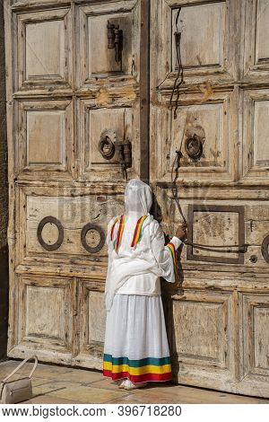 Jerusalem, Israel - November 21st, 2020: A Woman Kissing The Closed Doors Of The Church Of The Holy