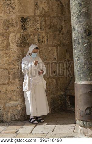 Jerusalem, Israel - November 21st, 2020: A Nun Praying Near The Church Of The Holy Sepulchre, Jerusa