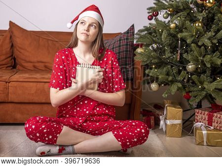 Happy Woman Sitting On Floor At Home In Solitude Dreaming And Writing Letter For Santa Claus With He