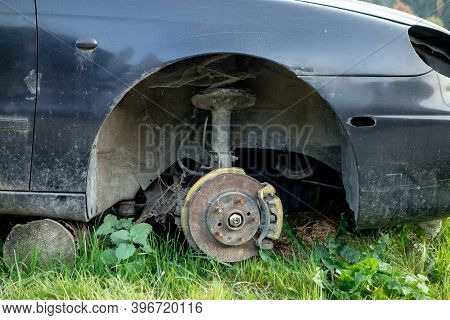 Detail Of A Damaged Car Without A Wheel With Brake System With Pads Exposed After A Traffic Accident