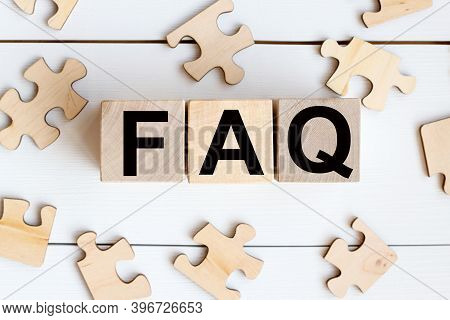 Faq, Text On Wooden Cubes On A White Background Near Wooden Puzzles