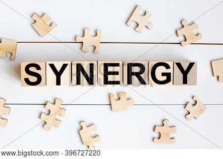 Synergy, Text On Wood Cubes On A White Background With Wood Puzzles
