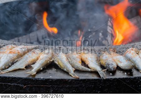 Process Of Cooking European Smelt Fish On Black Brazier At Summer Outdoor Food Market: Close Up. Sea