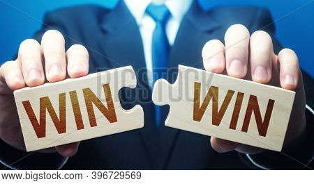 Man Holding Two Puzzles With Win-win Words. A Negotiation Strategy Makes All Parties Succeed. Mutual