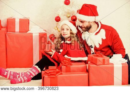 Father Christmas Concept. Family Christmas Celebration Traditions. Dad In Santa Costume With Daughte