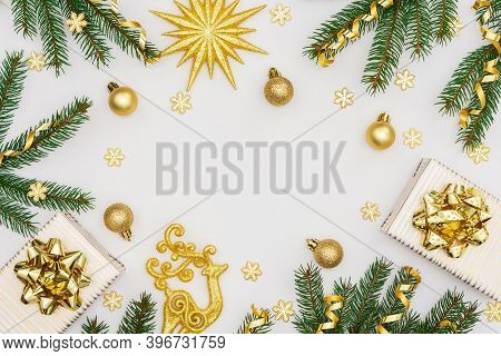 Festive Background With Gold Decoration, Green Spruce Branches And Shiny Golden Serpentine Confetti,