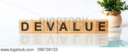 Wooden Blocks With The Text: Devalue. The Text Is Written In Black Letters And Is Reflected In The M