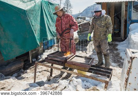 Bashkortostan, Russia / 30.03.2020: Beekeepers Prepare Hives For The New Season. Cleaning The Pallet