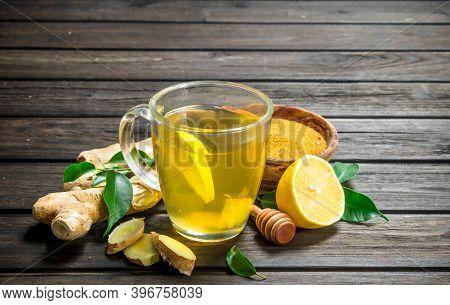 Ginger Tea And Ground Ginger. On Black Wooden Background