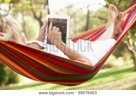 Senior Woman Relaxing In Hammock With  E-Book