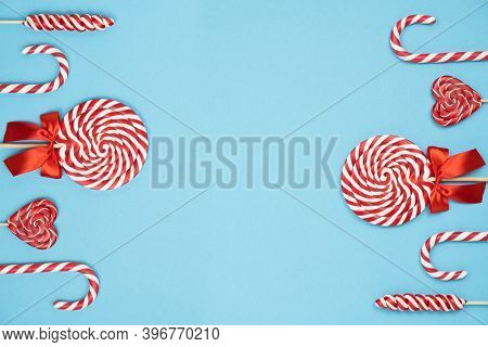 Christmas Red Striped Candy Canes And Lollipops On Blue Background. Merry Christmas Sweets And Happy