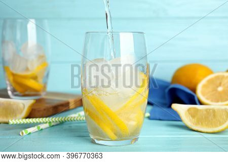 Pouring Soda Water Into Glass With Lemon Slices And Ice Cubes At Light Blue Wooden Table