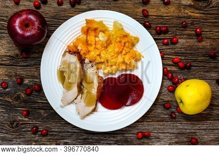 Simple Thanksgiving  plate with turkey,mashed potatoes,jellied cranberry sauce and gravy