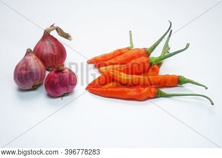 Some Red Chilies And Shallots On A White Background
