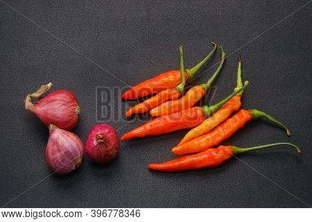 Some Red Chilies And Shallots On A Black Background