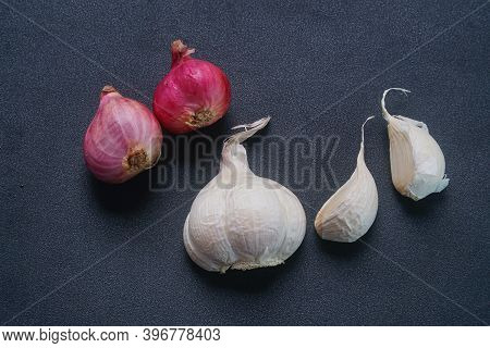 Some Shallots And Garlic On A Black Background