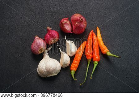 Some Red Chilies, Shallots And Garlic On A Black Background