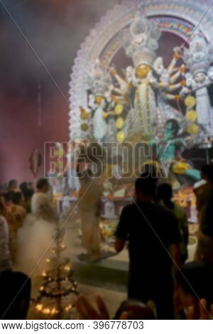 Blurred Image Of Goddess Durga Idol Being Worshipped With Holy Lamp And Holy Smoke Inside Decorated