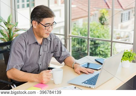 Asian Executive Senior Businessman Sitting On Desk Office With His Office, The Confident Middle Aged