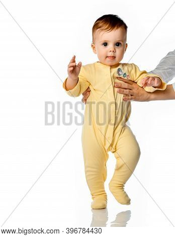 Little Toddler Child Learning To Walk Make First Step Wearing Comfortable Jumpsuit Studio Portrait.