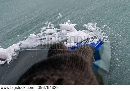 A Hand In Woolen Glove Removing Ice On The Windshield Of A Car On A Cold Morning In Winter