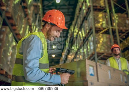 Male Warehouse Worker In Helmet Scanning Barcodes On The Boxes